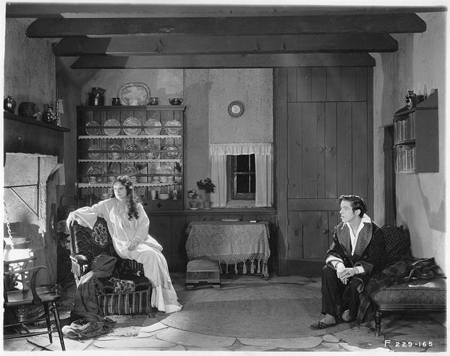 May McAvoy dans le rôle de Grizel, en chemise de nuit près du feu, et un jeune homme assis sur un lit dans 'Sentimental Tommy' de John S. Robertson
