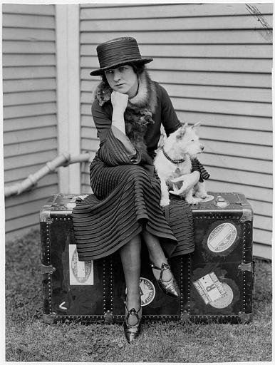 Portrait de May McAvoy assise sur une valise avec un chien