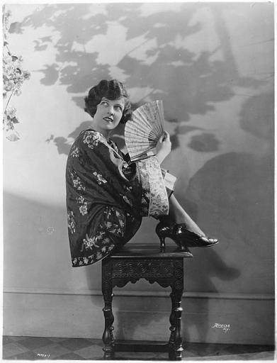 Portrait de May McAvoy dans un kimono asiatique avec un éventail devant un décor de fleurs porté en ombre chinoise derrière elle
