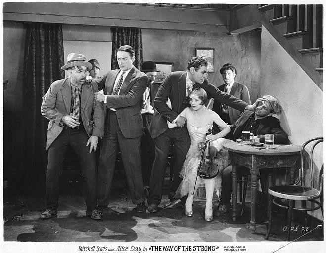 Dans un bar, Alice Day, dans le rôle de Nora, tenant un violon, entourée d'hommes dont le beau William, interprété par Mitchell Lewis et Dan, interprété par Theodore Von Eltz dans 'The way of the strong' de Franck Capra (Columbia)