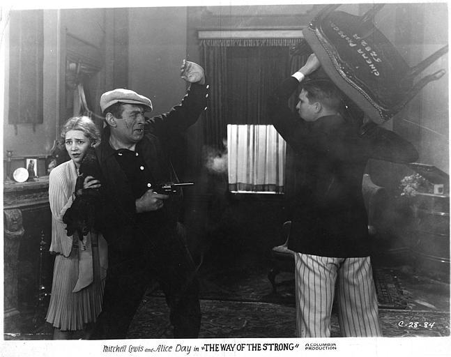 Alice Day dans le rôle de Nora se réfugiant derrière un homme pointant un revolver vers un autre qui le menace d'une chaise dans 'The way of the strong' de Franck Capra (Columbia)