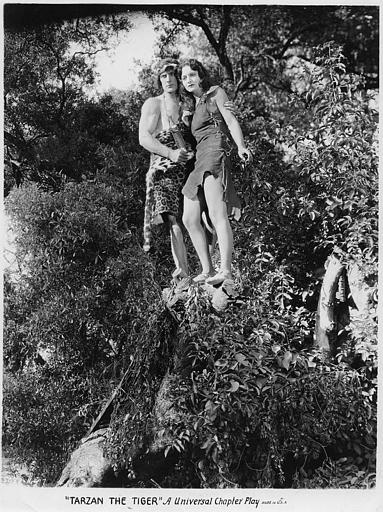 Natalie Kingston est Mary Trevor et Franck Merril, Tarzan, perchés sur un rocher dans 'Tarzan the mighty' (Universal Chapter Play)
