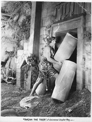 Franck Merril dans le rôle de Tarzan soulevant des morceaux de colonnes à l'entrée d'un temple dans 'Tarzan the mighty' de Jack Nelson (Universal Chapter Play)