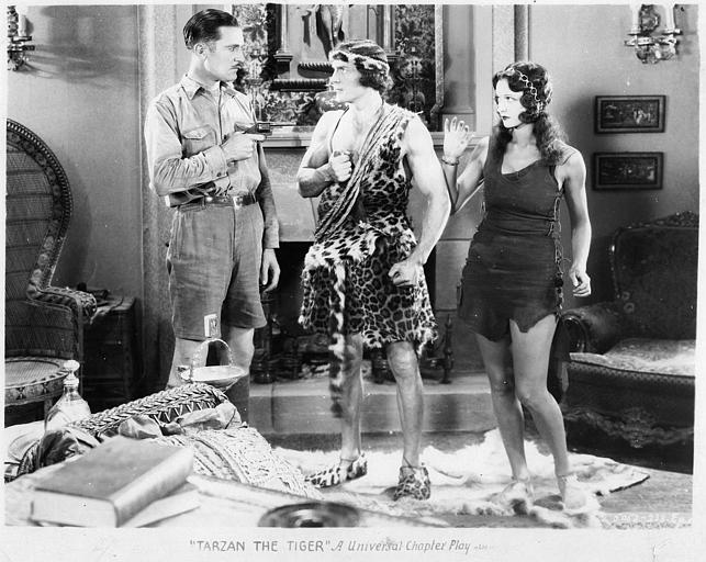 Un homme pointant un revolver sur Tarzan interprété par Franck Merril en présence de Natalie Kingston dans le rôle de Mary Trevor dans 'Tarzan the mighty' de Jack Nelson (Universal Chapter Play)