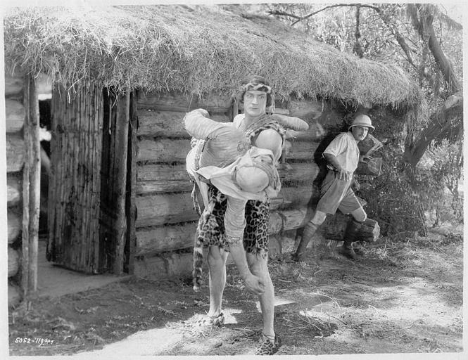 Franck Merril dans le rôle de Tarzan portant un homme à l'entrée d'une cabane tandis qu'un autre s'enfuit dans 'Tarzan the mighty' de Jack Nelson (Universal Chapter Play)