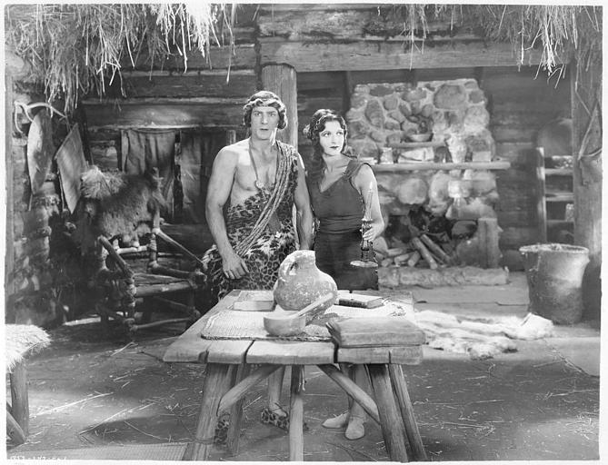 Natalie Kingston dans le rôle Mary Trevor et Franck Merril dans celui de Tarzan devant une table en bois dans 'Tarzan the mighty' de Jack Nelson (Universal Chapter Play)