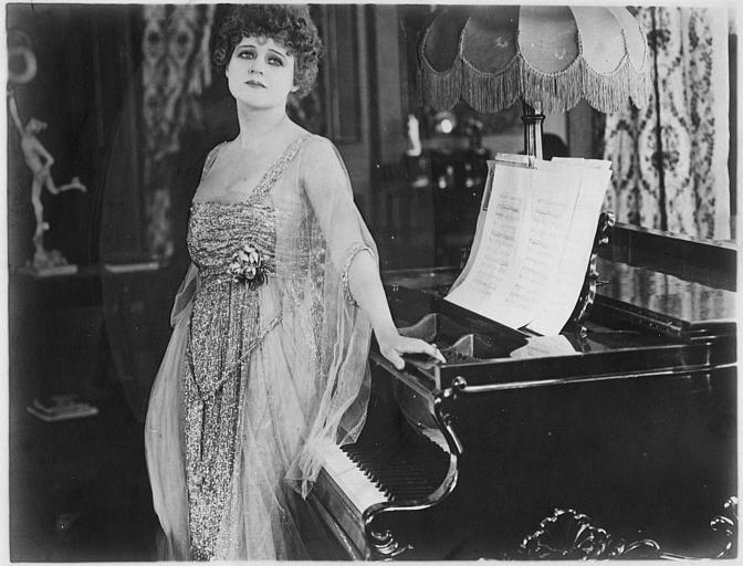 Lillian Walker dans le rôle d'Elizabeth Holt appuyée sur un piano dans 'The Embarrassment of Riches' d'Edward Dillon