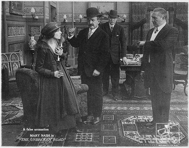 Mary Nash dans le rôle de Constance Turner et trois hommes menaçants lui parlant dans un salon dans 'The unbroken Road' de Thomas W  Dickinson (Life Photo Film Corporation)