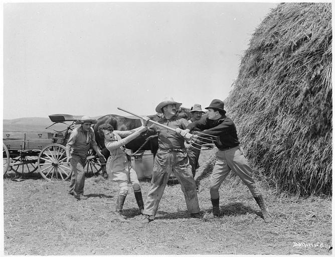 Deux hommes dont Herbert Rawlinson dans le rôle de Duncan McKail se battant avec une fourche devant une grande meule de foin en présence de plusieurs personnages dont Dorothy Devore interprétant Chaddie Green dans 'The prairie Wife' de Hugo Ballin (Metro-Goldwyn-Mayer)