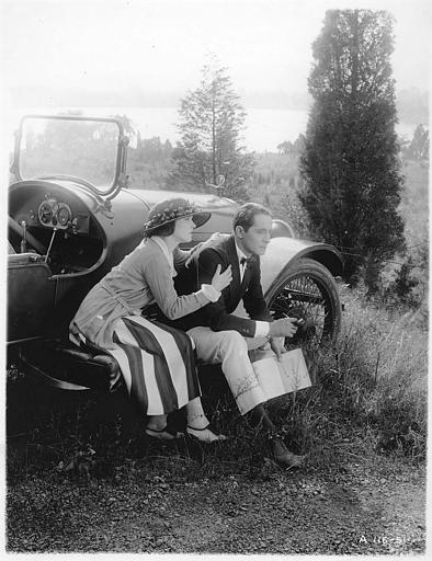 Zena Keefe dans le rôle de Clare Conway et Norman Kerry dans celui Peter Mendoza assis à côté d'une voiture en pleine campagne dans 'Proxies' de Georges D. Baker