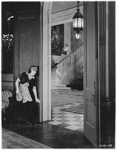 Une domestique écoute à la porte pendant que Zena Keefe dans le rôle de Clare Conway descend un escalier en arrière plan dans 'Proxies' de Georges D. Baker
