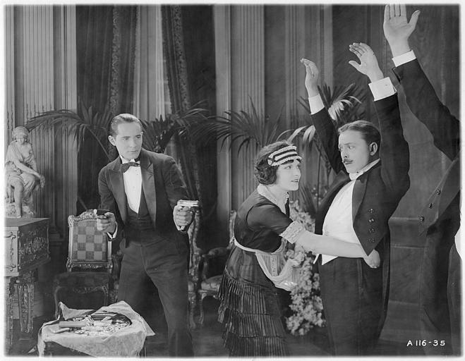 Norman Kerry dans le rôle de Peter Mendoza menace deux autres hommes avec un révolver pendant qu'une domestique leur fait les poches dans 'Proxies' de Georges D. Baker