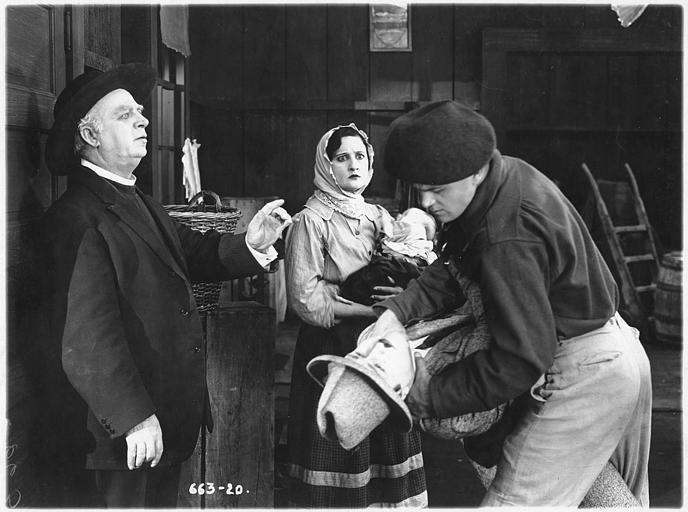 Pete Morrison (dans le rôle de Jean Laroque) étrangle un autre homme devant Rosemary Theby (Judith Bretans), portant un bébé, et un prêtre dans 'Love's pay day' d'E Mason Hopper (Triangle Play, Culver City Studios)