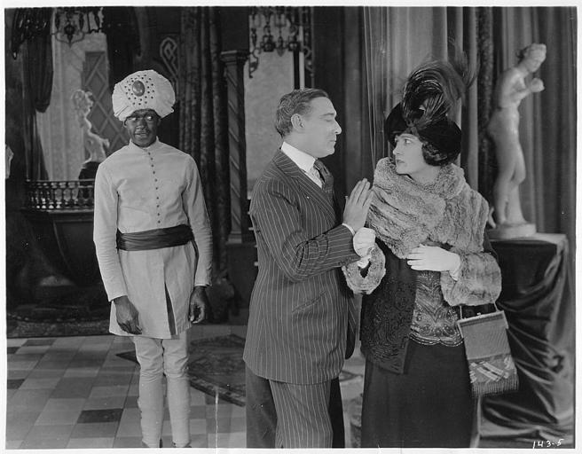 Un homme pousse Rosemary Theby (interprétant  Mrs. Beatrice Mason) par l'épaule en présence d'un personnage costumé en hindou : Rosemary Theby dans 'Your Friend and Mine' de Clarence G.Badger (S-L Pictures)