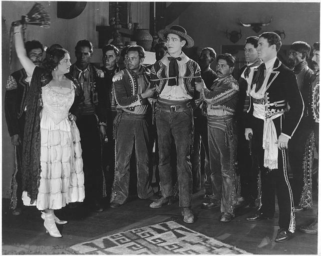 Plusieurs personnages mexicains et Arthur Carew interprétant Don Jose Alvarado entourant Allen Sears dans le rôle de Danny O'Neil qu'ils ont capturé et Rosemary Theby dans le rôle de Maria Inez levant son éventail dans 'Rio Grande' d'Edwin Carewe