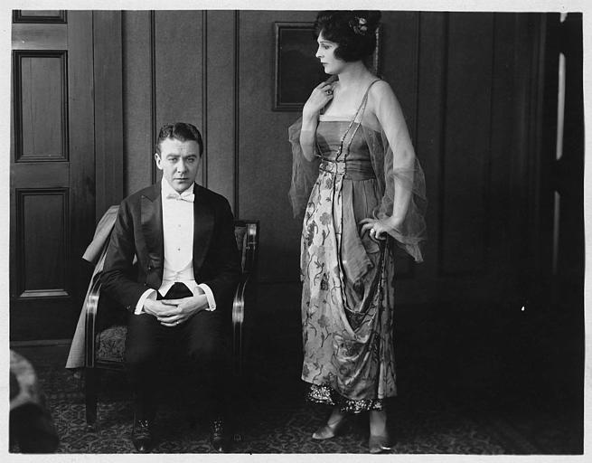 Tom Moore assis dans un fauteuil avec Rosemary Theby debout à ses côtés