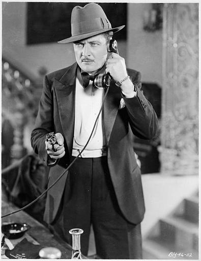 Eddie Lowe au téléphone avec un pistolet à la main