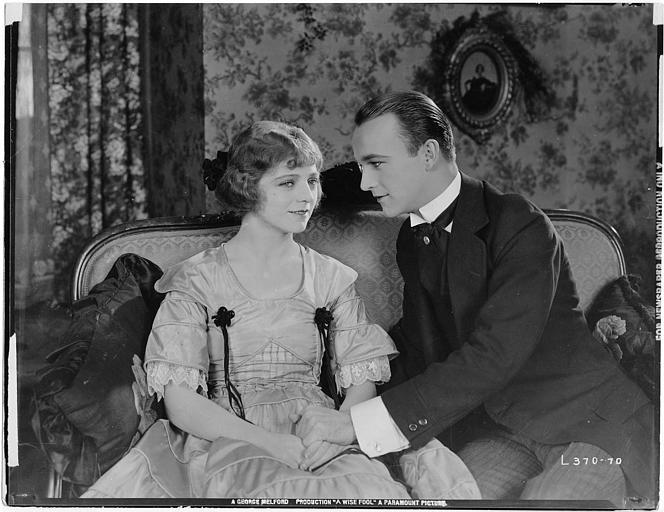 William Boyd dans le rôle de Gerard Fynes et Ann Forrest dans le rôle de Zoe Barbille souriant sur un canapé dans 'A wise fool' de George Melford (Paramount picture)