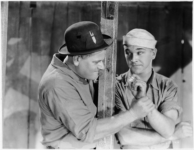 Un homme avec un chapeau melon tenant le poignet de William  Boyd qui joue Blondy dans 'Skyscraper' d'Howard Higgin