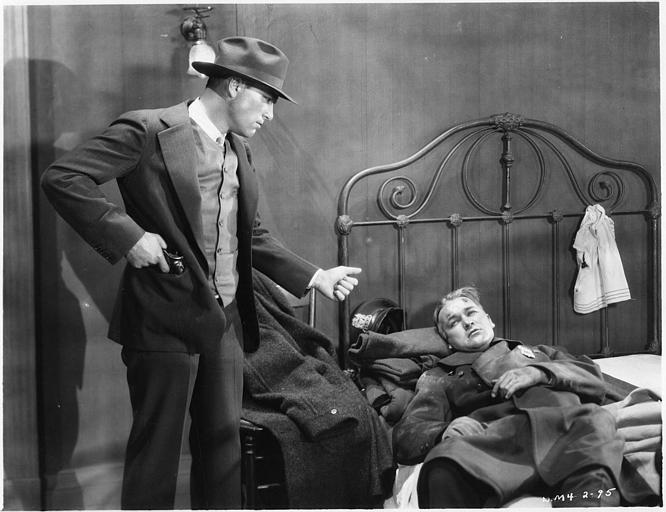 William Boyd dans le rôle de Pete Smith est couché sur un lit et, à côté de lui, un autre homme debout sort un pistolet de sa poche dans 'The Cop' de Donald Crisp
