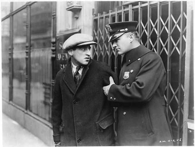 William Boyd dans le rôle de Pete Smith en policier tient le bras d'un homme portant une casquette dans 'The Cop' de Donald Crisp