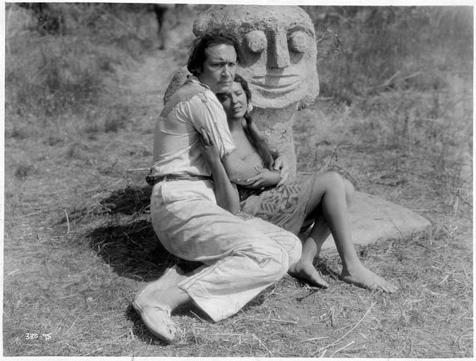 Monte Blue interprétant le Dr. Matthew Lloyd et Raquel Torres dans le rôle de Fayaway se tenant dans les bras devant une statue de pierre dans 'White shadows in the south seas' de W-S Vandyke (Metro-Goldwyn-Mayer)