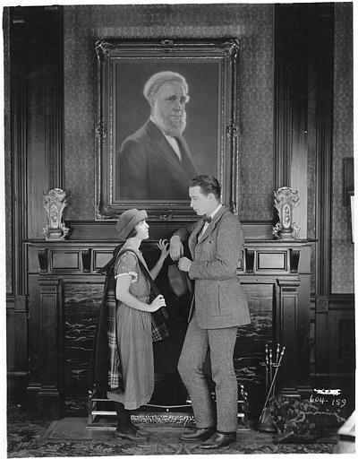 Monte Blue et Madge Kennedy discutant au bas d'un tableau dans un salon
