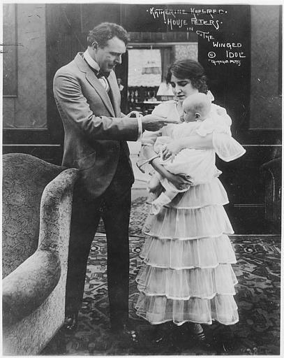 Un couple avec un enfant dans un salon : House Peters dans le rôle de Jack Leonard et Clara Williams dans celui de Mildred Leonard dans 'The winged idol' de Scott Sidney (Triangle Play)
