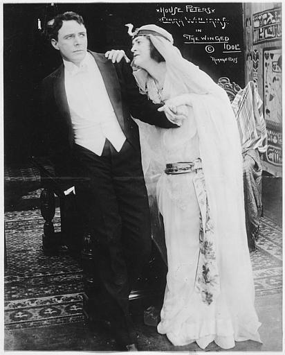Katherine Kaelred dans le rôle de la Comtesse Iva Ivanoff, vêtue de blanc, tient par l'épaule House Peters qui interprète Jack Leonard dans 'The winged idol' de Scott Sidney (Triangle Play)