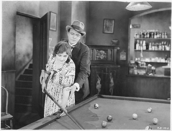 House Peters dans le rôle de John Hampstead guidant Grace Carlyle dans le rôle de Mariann Dounay pour jouer au billard dans 'Held to answer' d'Harold Shaw (Metro Picture)