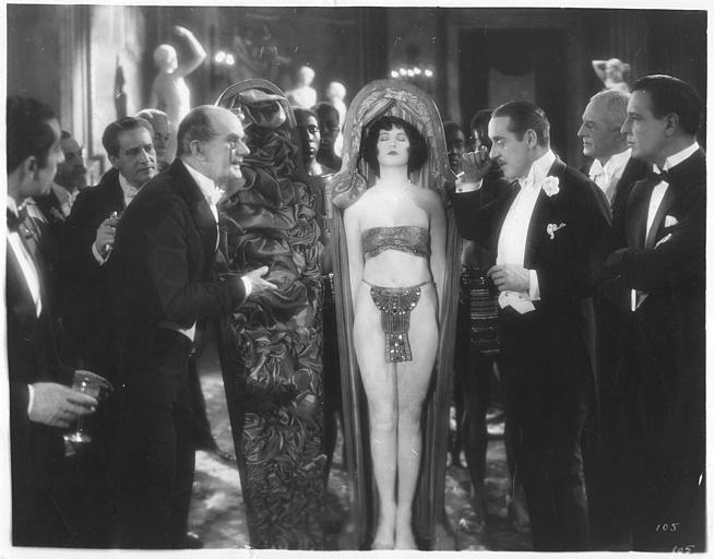 Dorothy Mackaill dans le rôle de Consuelo Cox, endormie dans un cercueil, entourée d'hommes dont Conway Tearl et Robert Cain dans 'The dancer of Paris' d'Alfred Santell (Robert's Kane's First National Production)