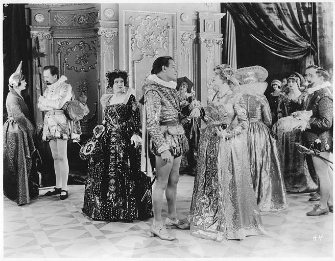 Plusieurs personnages en costume dans un salon avec au centre Conway Tearle dans le rôle de Rupert de Vrieac et Betty Francisco dans celui de Margot de Vancoire dans 'Ashes of vengeance' de Franck Lloyd