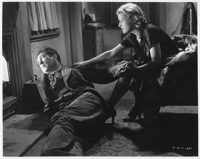 Victor McLaglen qui joue Gypo Nolan, couché près d'une cheminée avec Margot Grahame dans le rôle de Katie Madden assise sur un fauteuil le réconfortant dans 'The informer' de John Ford (RKO-Radio)