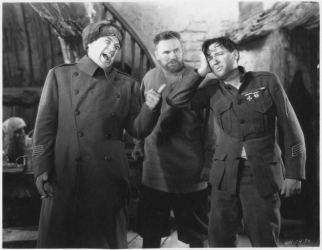Un homme se moquant d'un militaire qui se tient la tête en présence d'un troisième homme barbu : Edmund Lowe dans le rôle du Sergent Flagg et Victor MacLaglen dans celui du sergent Harry Quirt dans 'The cockeyed world' de Raoul Walsh