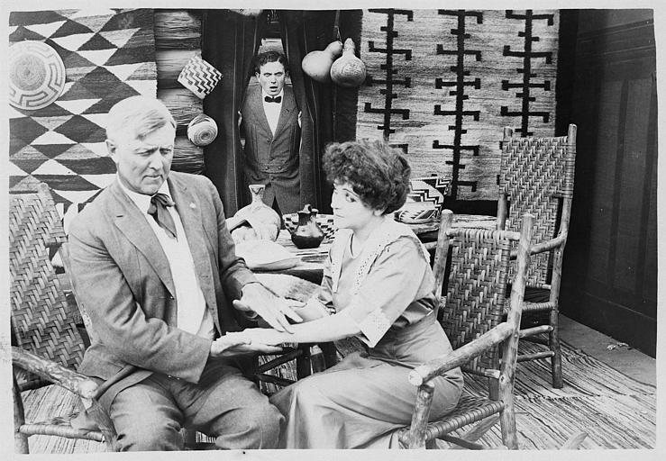 Herbert Rawlinson surprend un couple assis sur des chaises en bois