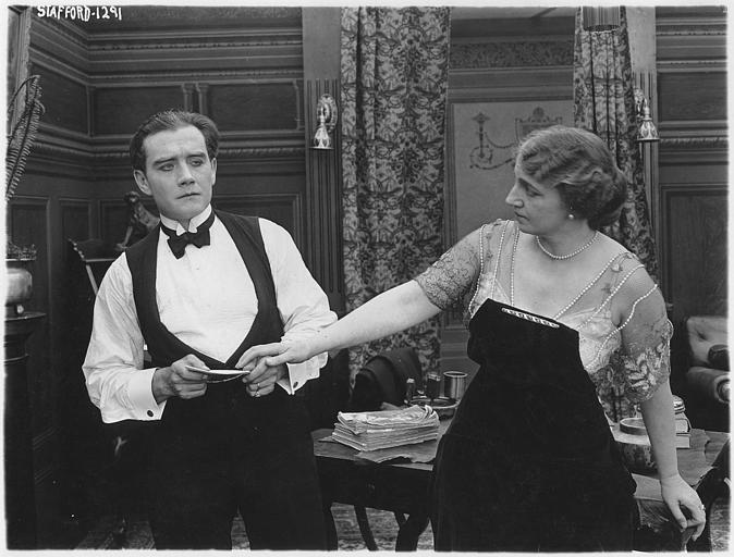Adele Farrington tentant d'attraper un papier que tient un homme dans un salon