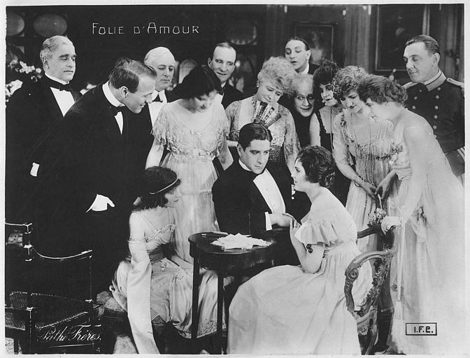 Un homme et une femme assis à une table entourés de plusieurs personnages dans 'Folie d'amour' de Léonce Perret (Pathé)