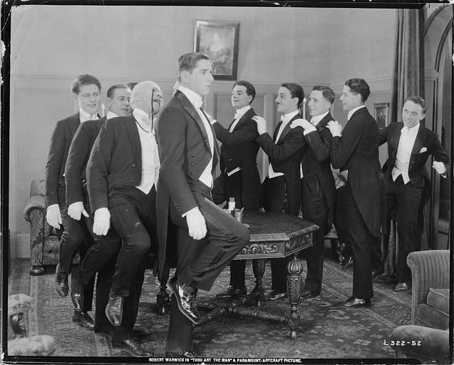 Plusieurs hommes dont Robert Warwick dans le rôle de Myles Calthrope se suivant en file indienne à cloche-pied dans 'Thou art the man' de Thomas N. Heffron (Paramount Picture)