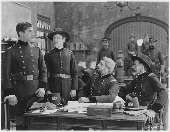 Plusieurs soldats dont Robert Warwick regardant un soldat dans un bureau