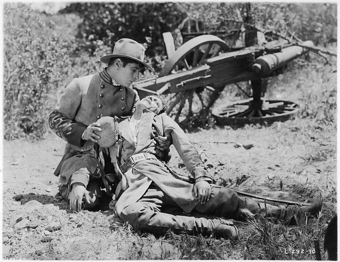 Robert Warwick, en soldat, donnant de l'eau à un autre, inanimé dans ses bras