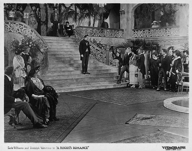 Dans un grand hall, un homme sur les marches d'un escalier regardé par plusieurs personnages : Earle Williams et Rodolph Valentino dans 'A Rogue's Romance' de James Young (Vitagraph, Albert L. Smith)