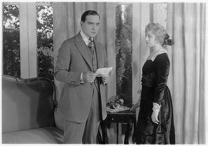Earle Williams, une lettre à la main et Ella Hall, dans un salon