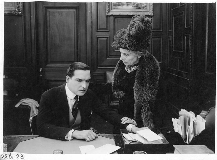 Earle Williams assis à un bureau avec une femme portant un chapeau à plume et un renard autour du cou, debout à ses côtés