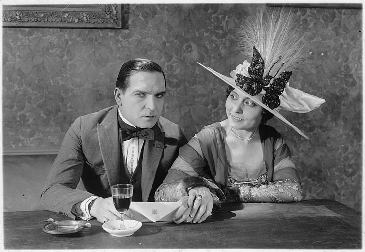 Earle Williams tenant une lettre à la main et une femme avec un grand chapeau lui souriant