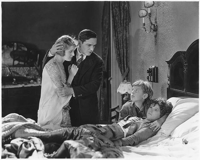 Dans une chambre, un enfant mort pleuré par un garçon et un couple : Earle Williams dans le rôle de Ramón Martinez et Jane Novak dans celui d' Alice Martinez dans 'Jealous Husbands' de Maurice Tourneur
