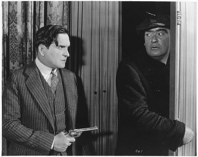 Earle Williams dans le rôle de Ramón Martinez pointant son revolver sur George Seigmann interprétant Red Lynch qui essaye d'entrer dans un appartement dans 'Jealous Husbands' de Maurice Tourneur