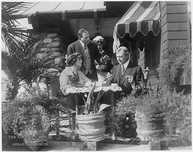 Sur une terrasse, plusieurs personnages, dont Hobart Bosworth et Adele Farrington dans le rôle du couple Balderson, discutent autour d'une table dans 'The coutry mouse' d'Hobart Bosworth (Bosworth Inc)