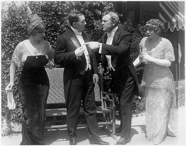 Deux hommes se disputant en compagnie de deux femmes en extérieur : Hobart Bosworth et Adele Farrington dans le rôle du couple Balderson dans 'The coutry mouse' d'Hobart Bosworth (Bosworth Inc)