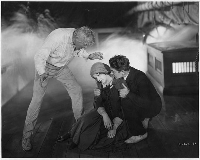 Sur un bateau, un femme assise sur le sol soutenue par deux hommes dont Hobart Bosworth jouant Wolf Larsen dans 'The Sea Wolf ' d'Hobart Bosworth