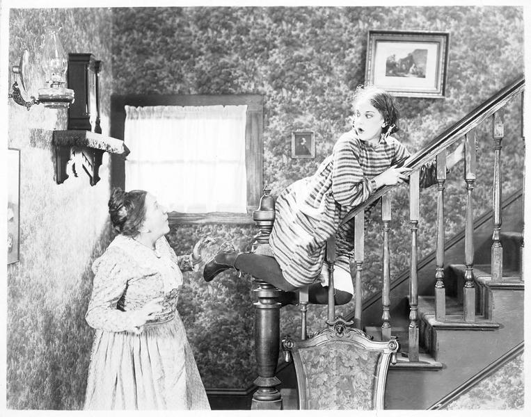 Eliza (V. Dana) se laissant glisser sur la rampe d'escalier
